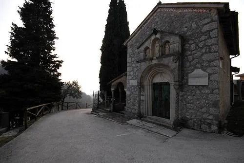 Fachada em pedra do Santuário di Collagù. Ao lado, um pinheiro altíssimo.