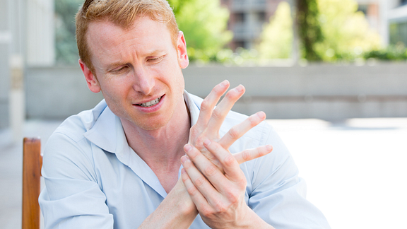Image of man sitting outdoors holding his had and wrist in pain