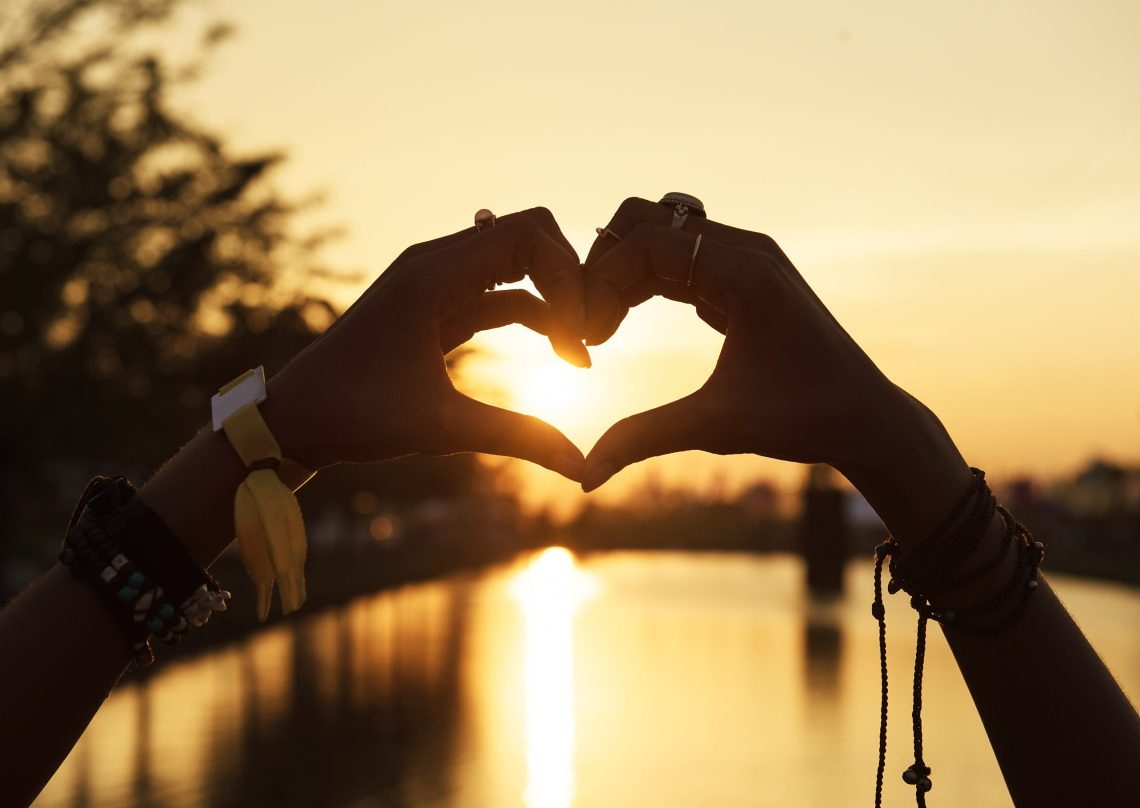 hands forming a heart over a lake scene
