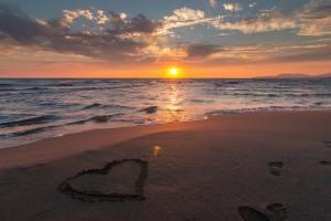 heart written in sand on beach next to ocean