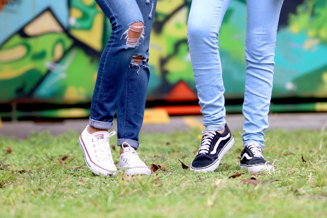 two pair of legs wearing jeans and tennis shoes