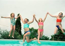 girls jumping in pool