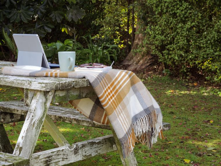 A old outdoor picnic table set up with laptop and coffee.