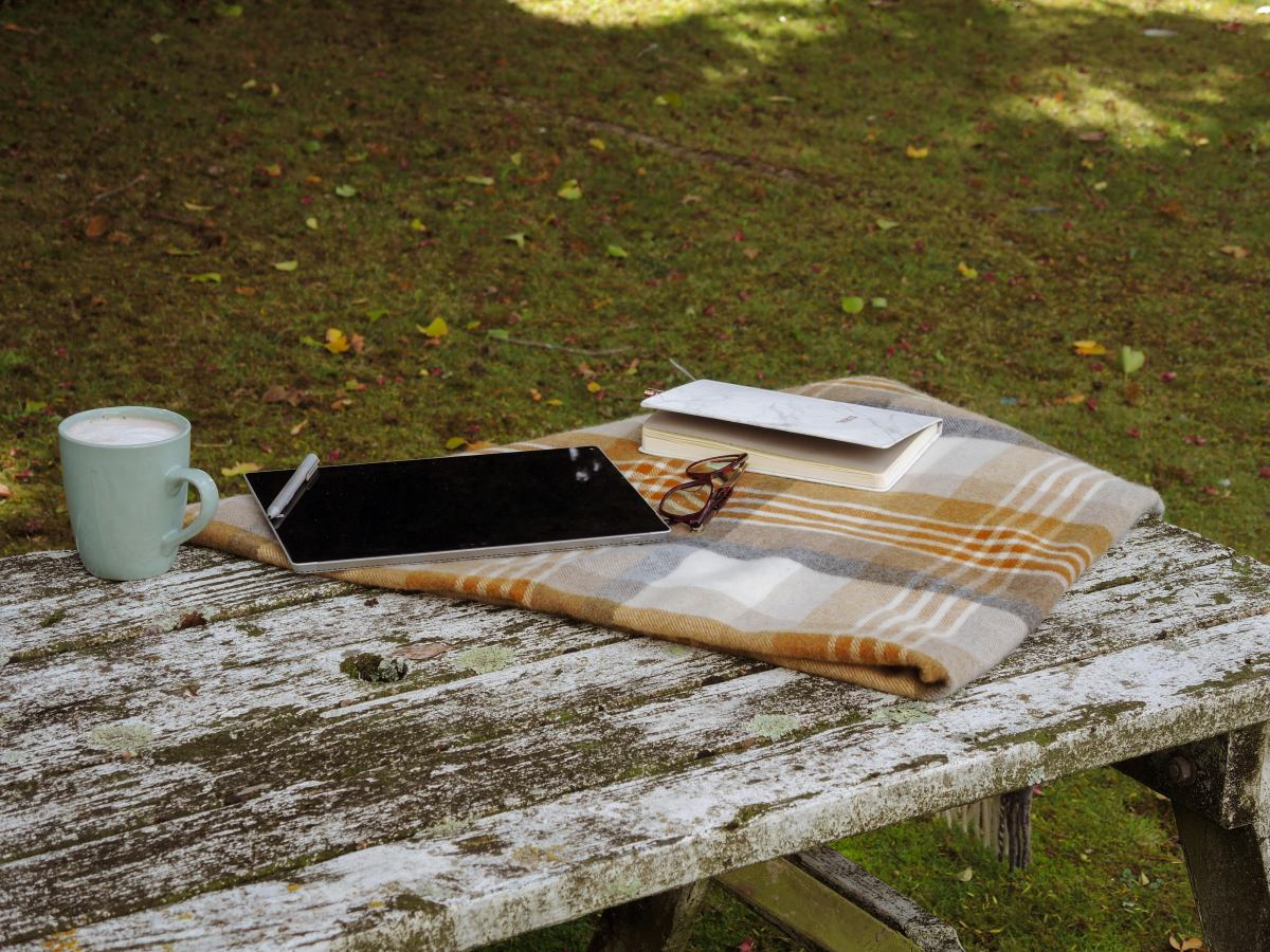 An old picnic table is draped with a yellow tartan wool blanket. On it sit a table, coffee, diary and reading glasses.