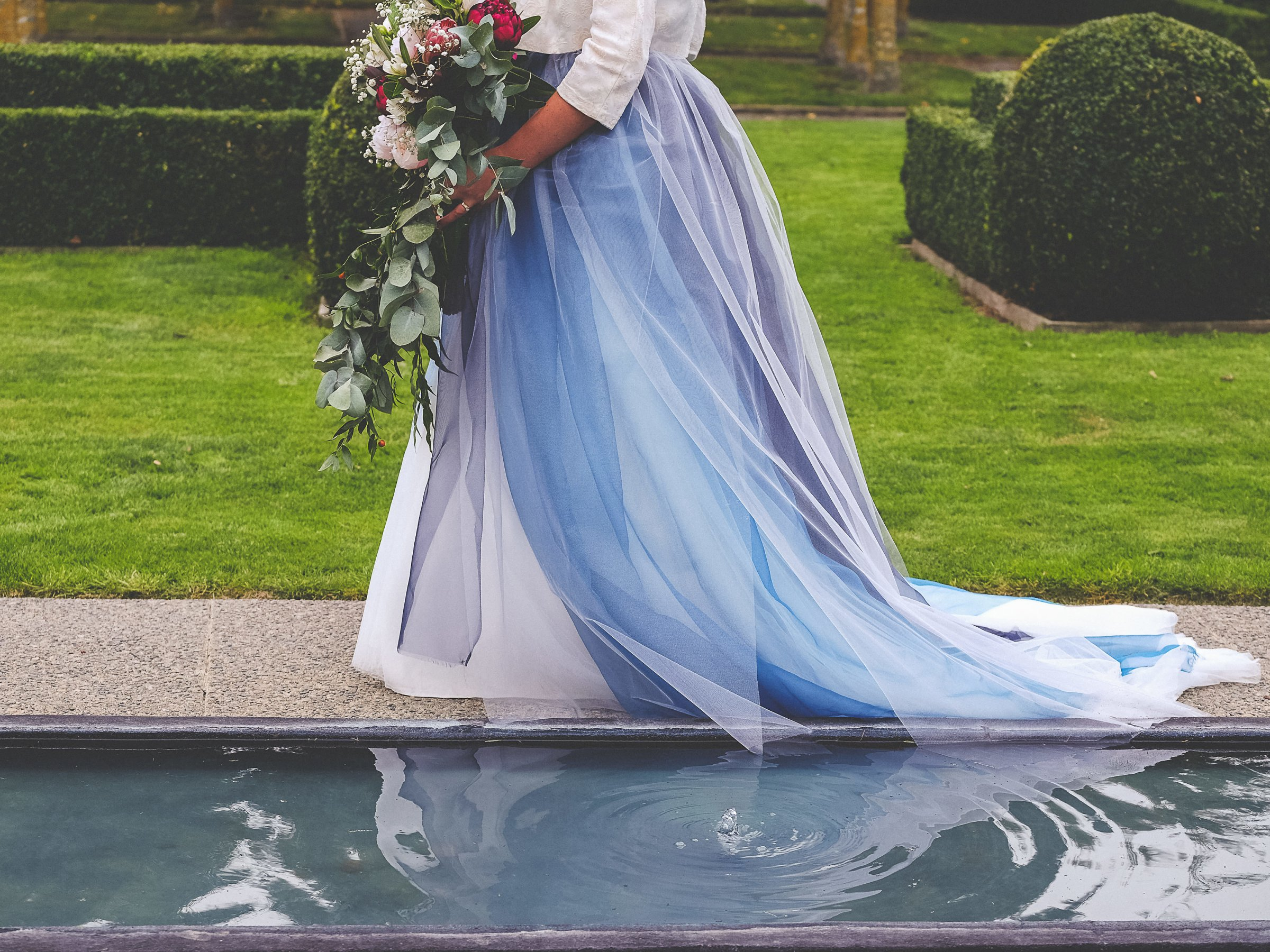 A bride wearing a dress in many shades of blue as she walks past a small water feature carrying her wedding bouquet.