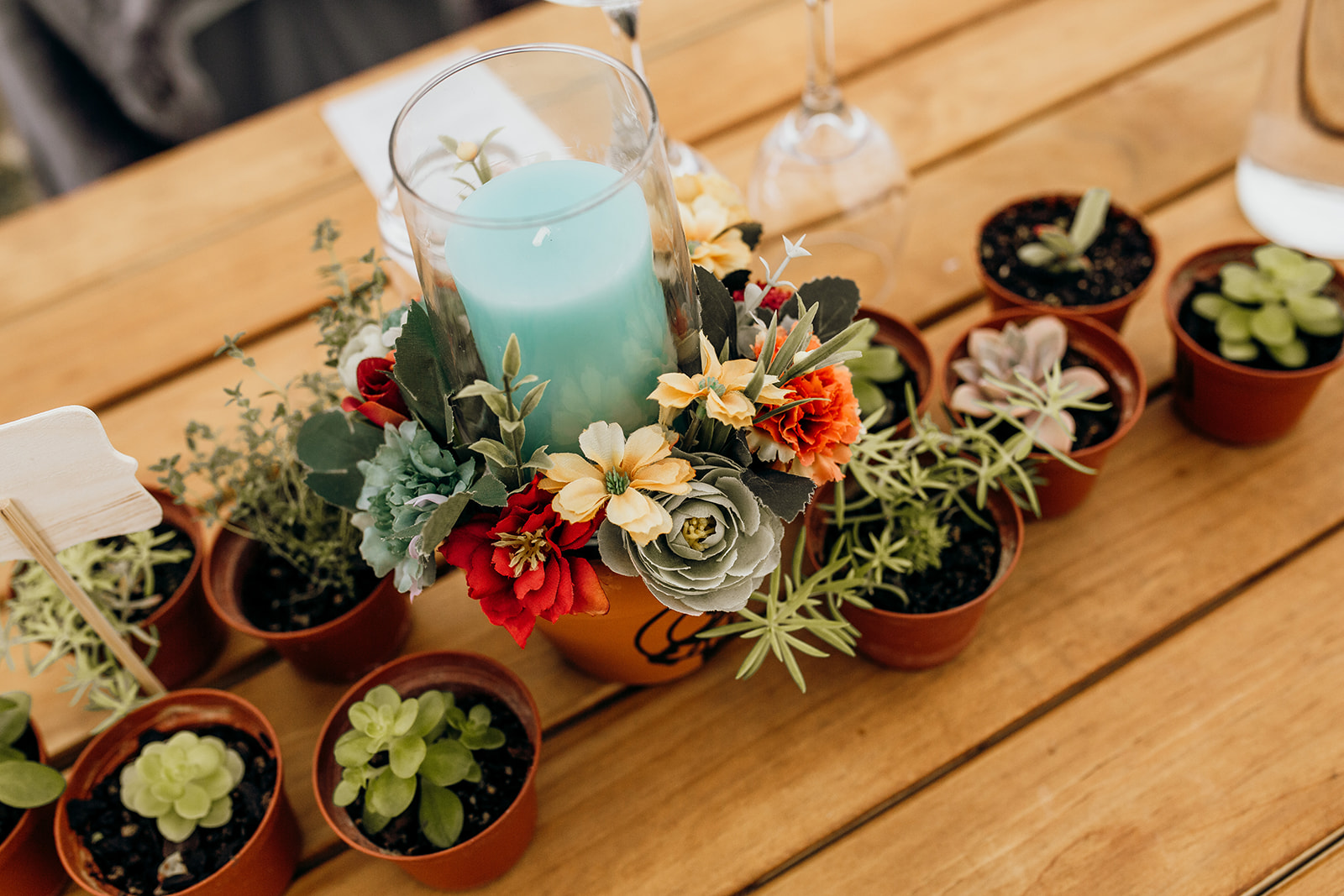 A cluster of succulents surround a terracotta pot with a candle, forming the table centre at a wedding.
