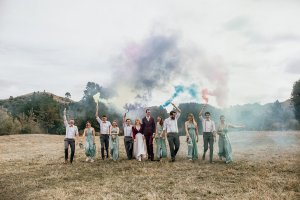 A wedding party of 10 plus the bride and groom walk through a paddock, coloured smoke bombs held high above their heads.