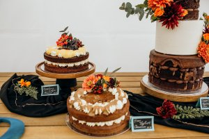 A partial view of a wedding cake table with three delicious looking wedding cake flavours, all decorated beautifully with eco-friendly florals.