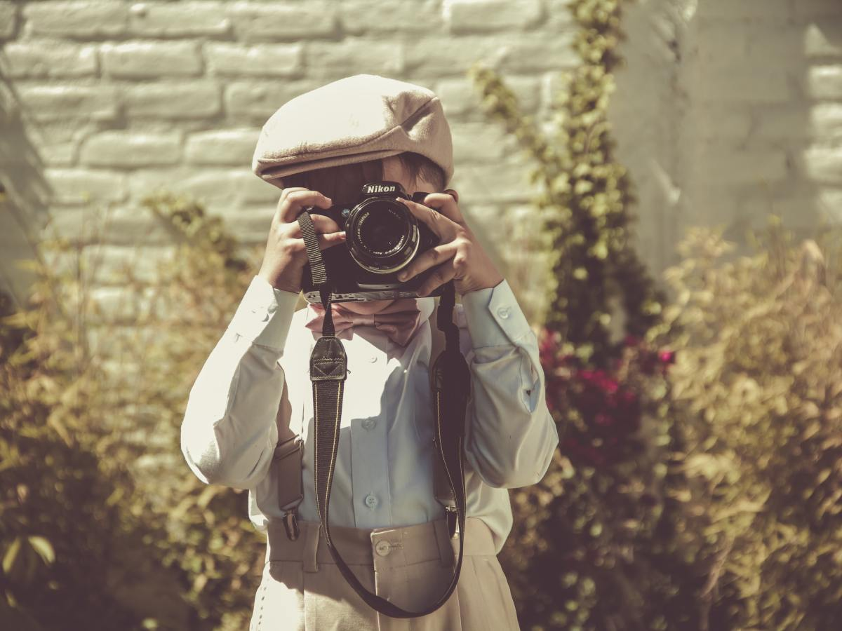 Small child suited up and holding a camera
