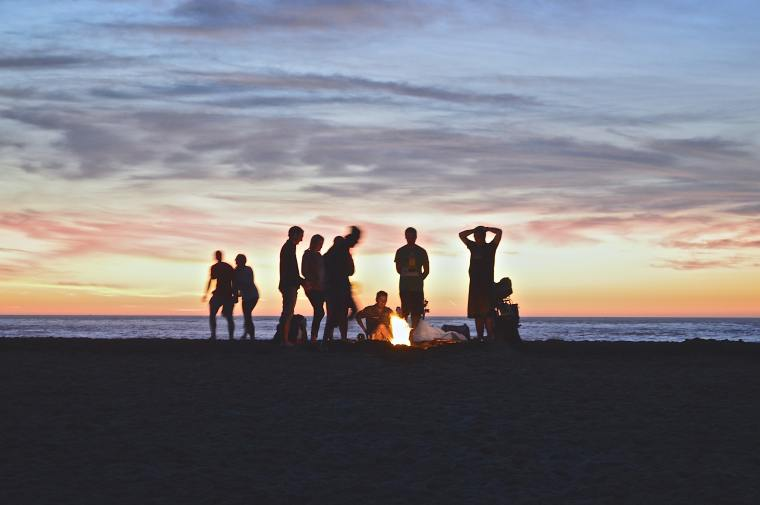 Group of people around a campfire at sunset.