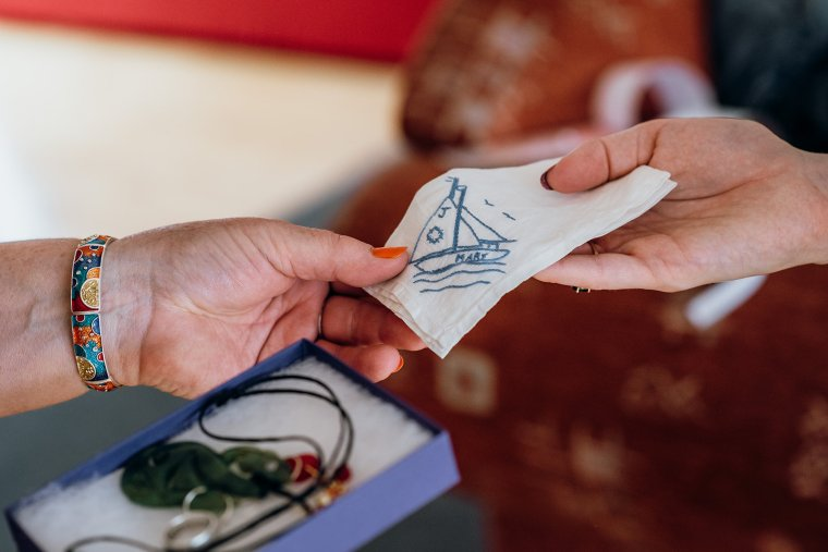 An embroidered handkerchief is passed from one hand to another