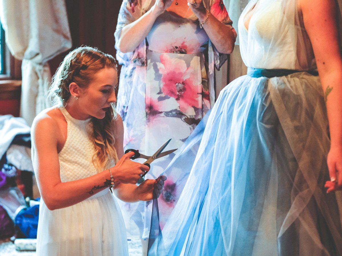 Jodie kneels next to a bride, trimming the loose ends of her dress just moments before she's due to walk down the aisle.