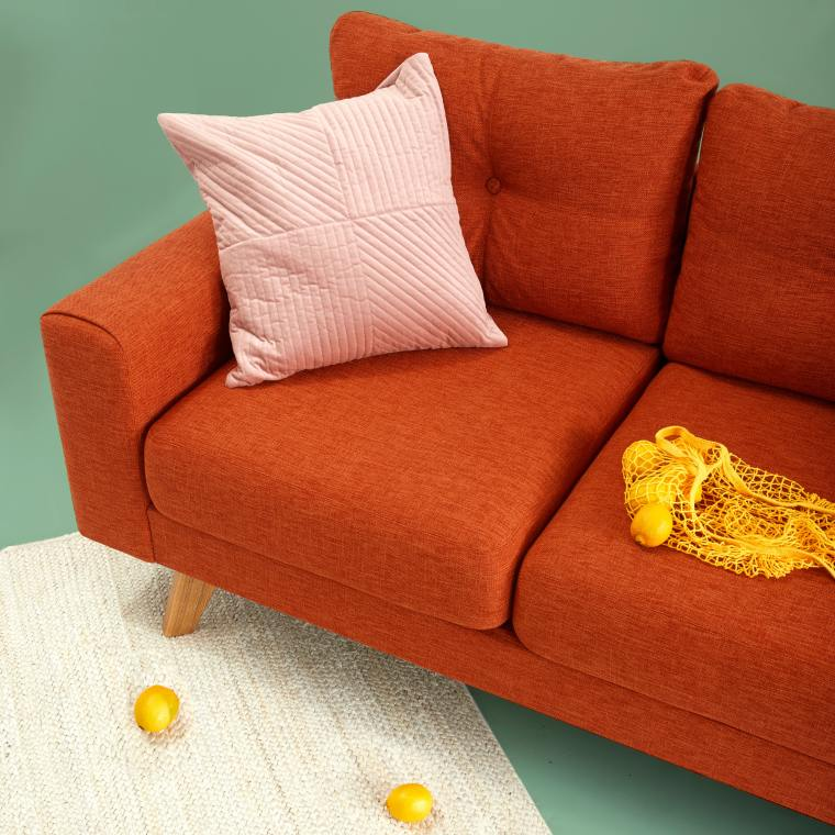 Lemons lie across a bright orange couch, a baby pink cushion contrasting the bright colours.