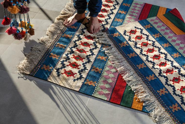 A person stands barefoot on two layered rugs. Their patterns very bright colourful and fun.