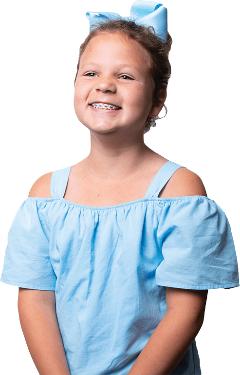 Young girl smiling, blue outfit, blue bow, braces, white teeth, Fishbein Orthodontics