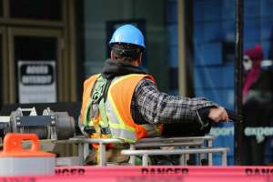 Man in hard hat and safety jacket on building site lift