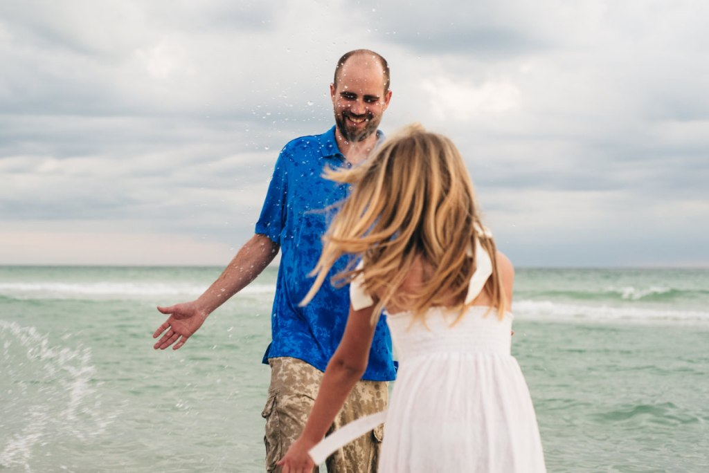 Daughter splashing dad in the ocean