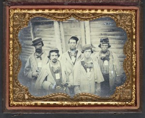 """The prisoner second from right sports a hat with a similar style. Entitled, """"Five unidentified prisoners of war in Confederate uniform in front of their barracks at Camp Douglas Prison, Chicago, Illinois."""" Courtesy of the Library of Congress."""