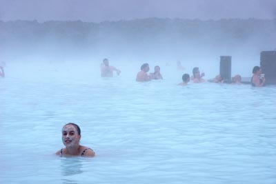 A visitor to the Blue Lagoon with silica mud on her face