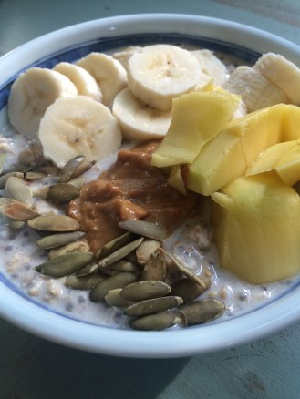 Overnight oats & chia soaked with almond milk, chopped dates & honey. Topped with banana, mango, PB and pepitas.
