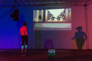 Person stepping on a stepper while having VR glasses, with a projection on the wall in front of them