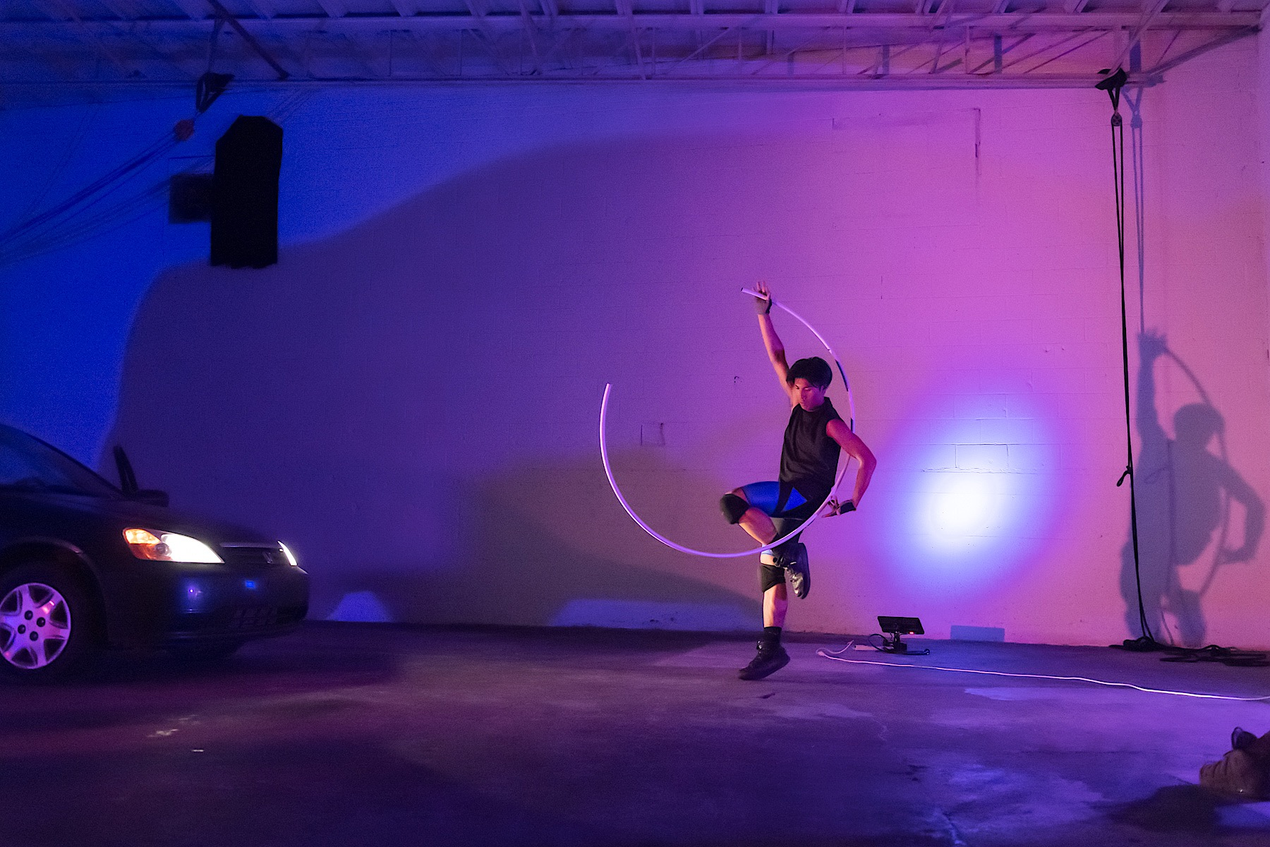 Person dancing with a big hula hoop next to a car