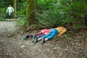 Two persons lying face down in the forest