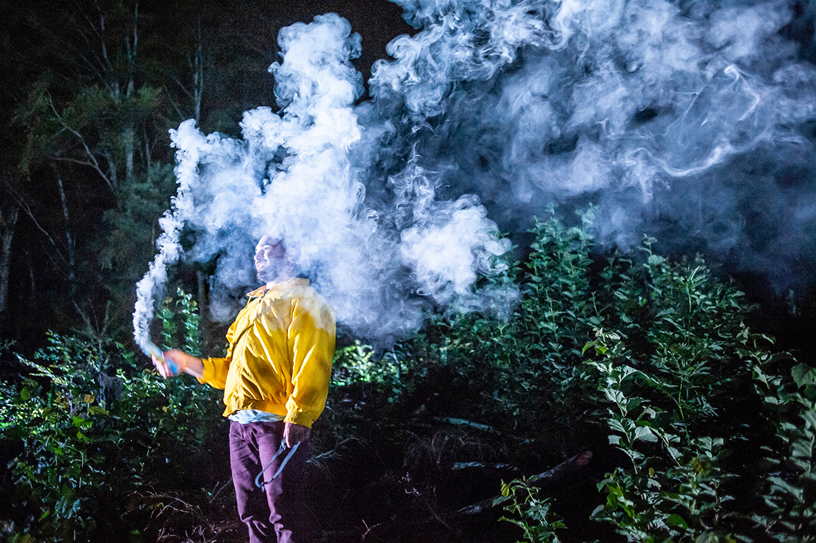 Person in yellow jacket in the forest, surrounded by smoke