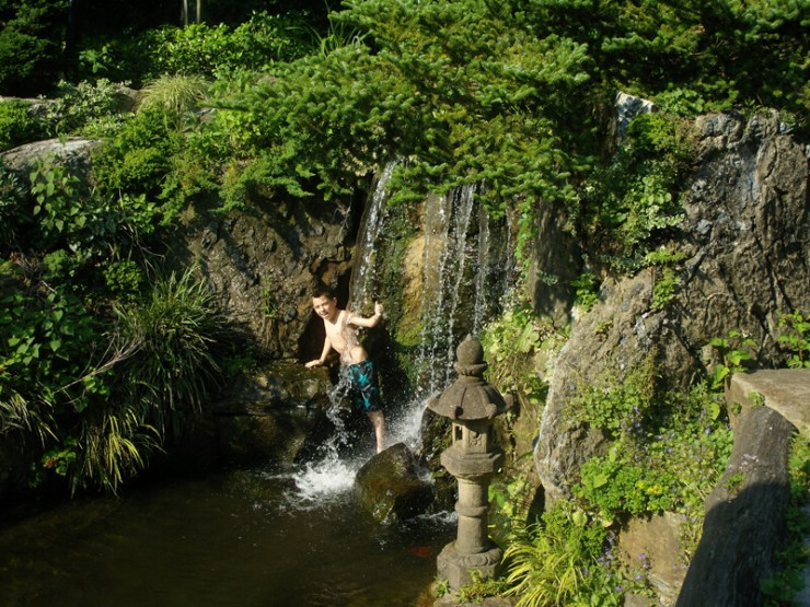 A waterfall on Long Island, NY with boy underneath the cascading water