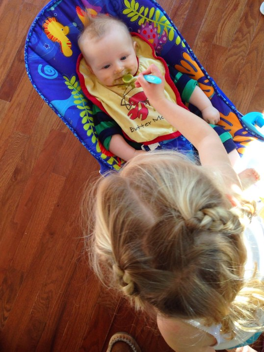 Sister feeding baby C
