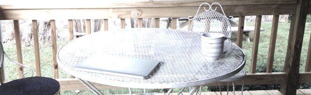 laptop and coffee mug on patio table