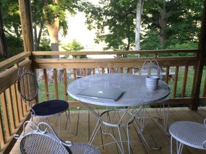 a table with a laptop and coffee mug, on a porch overlooking trees and a river