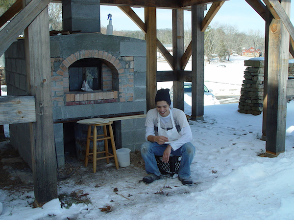 Brian sitting by the outdoor oven in the snow