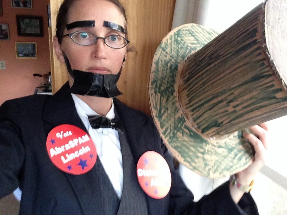 """Emily dressed as Abraham Lincoln with a vest and suit, with a duct tape beard and bowtie, holding a top hat and wearing buttons that say """"AbraSPAM Lincoln"""" and """"Dishonest Abe"""""""