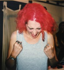 Emily with bright red hair, dressed like Lola and making fists and yelling