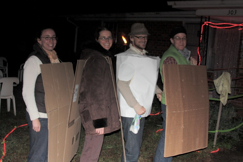 four people standing in a row, wearing a cardboard square, a chocolate brown coat, a white paper tube, and a cardboard square