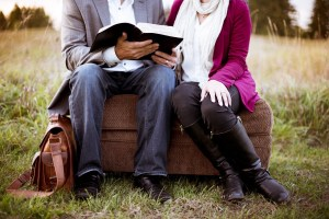 couple sitting on a small sofa outside, holding an open book