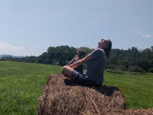 Emily wearing eclipse glasses, sitting on a hay bale