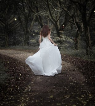 woman with long hair in long dress, running down path in dark forest