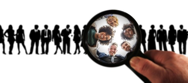 a row of silhouettes of people with a magnifying glass showing the faces of five people, all smiling