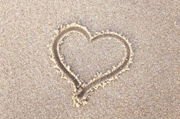 a heart drawn in beach sand