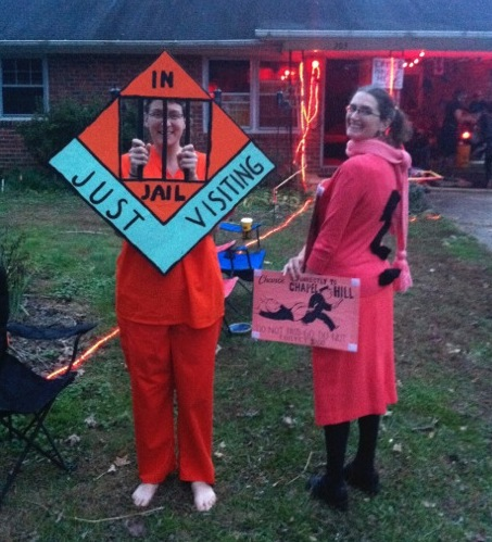 "Jessica in orange scrubs holding an ""in jail, just visiting"" sign with bars over her face, and Emily in orange with a question mark on her back holding a large Chance card"
