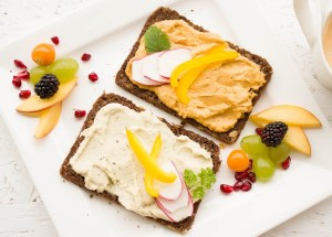 crackers with hummus spread on them and raw peppers, plus fruit scattered nearby