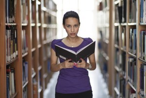 woman reading book in shelves of books