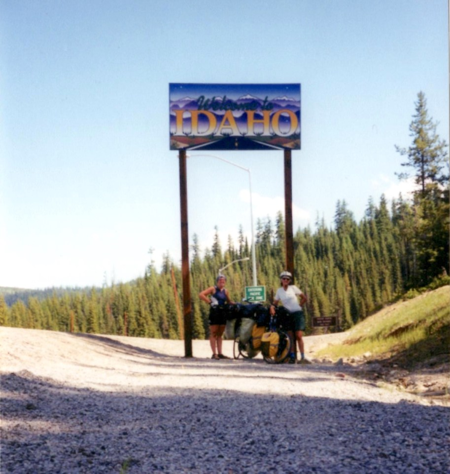 "two women with loaded bicycles under a tall sign that says ""Welcome to Idaho"" with evergreen trees in back"