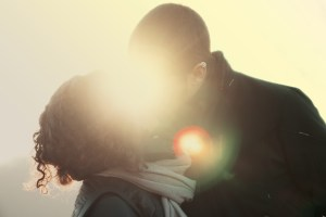 silhouettes of a couple kissing with the sunlight streaming in from behind them