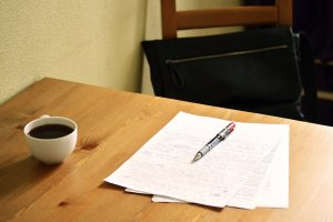 papers on table with red pen and coffee