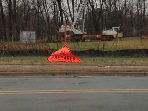 "a construction sign that has folded over on itself so that it reads ""Be Prepared"", with a rainy roadside"