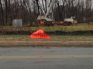 """a construction sign that has folded over on itself so that it reads """"Be Prepared"""", with a rainy roadside"""