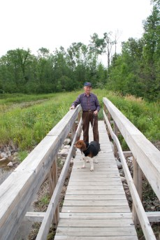 On a bridge over the pond with Micah the dog.